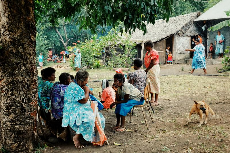 mujer local de los aldeanos que espera una celebración de la circuncisión en la plaza principal imagen de archivo libre de regalías