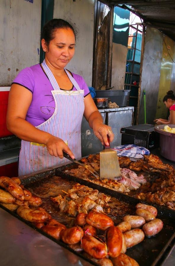 Mujer local que cocina la carne para el asado en Mercado 4 en Asuncion, par foto de archivo