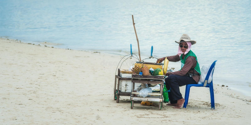 Mujer local que vende la fruta fresca en una playa tropical fotografía de archivo libre de regalías