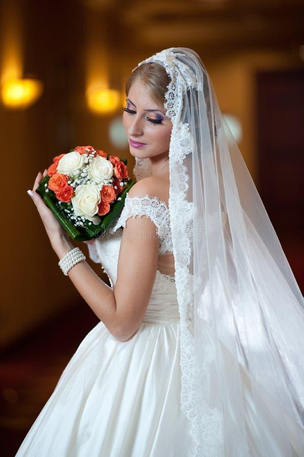 Mujer lujosa hermosa joven en el vestido de boda que presenta en interior lujoso Novia con el velo largo que sostiene su ramo de  fotografía de archivo libre de regalías
