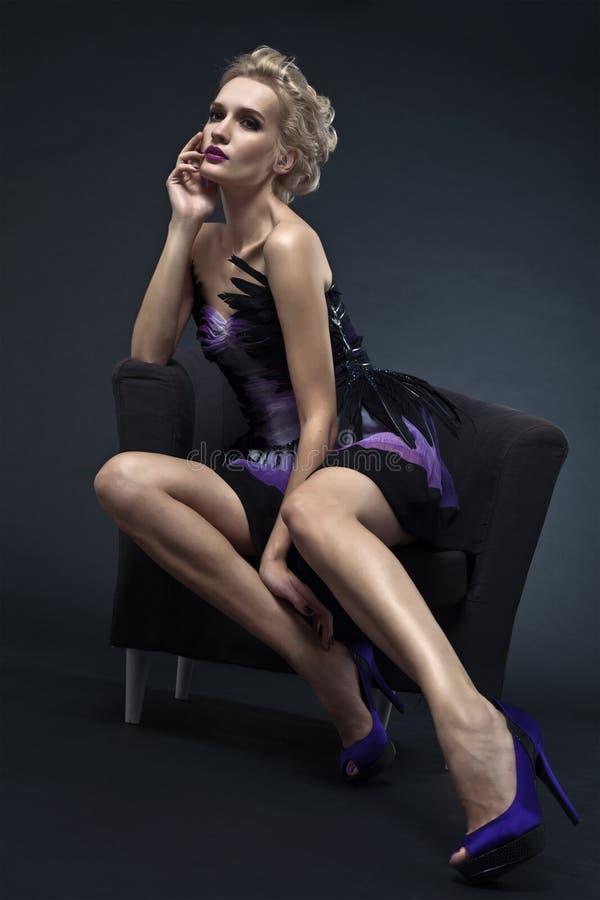 Mujer lujosa hermosa que se sienta en silla foto de archivo