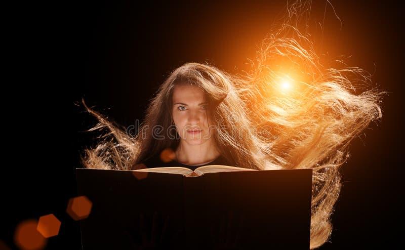 Mujer mágica que lee un libro Fondo negro foto de archivo