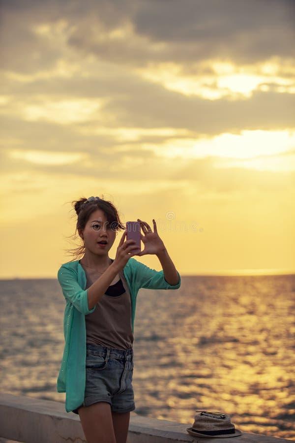 Mujer más joven asiática que toma la fotografía por el teléfono elegante en la puesta del sol s imagenes de archivo