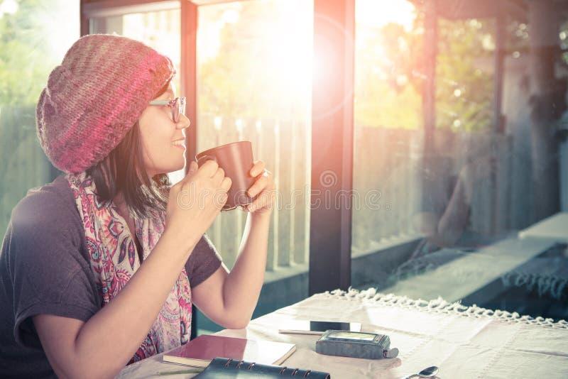 Mujer más joven asiática y taza de café caliente a disposición que sonríen con el happ foto de archivo