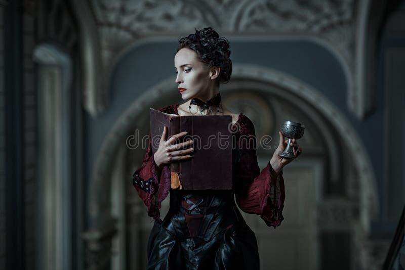 Mujer mística con un libro fotos de archivo