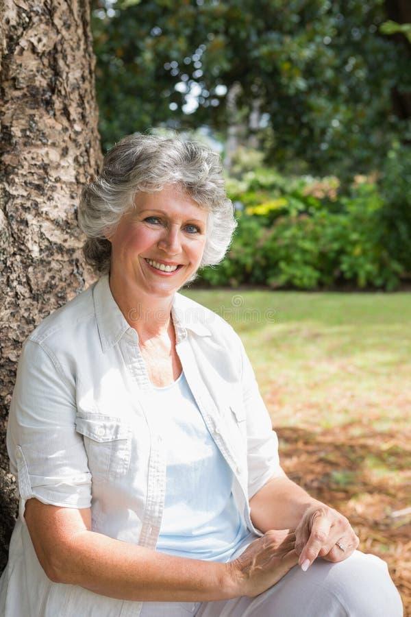 Mujer madura alegre que se sienta en tronco de árbol foto de archivo