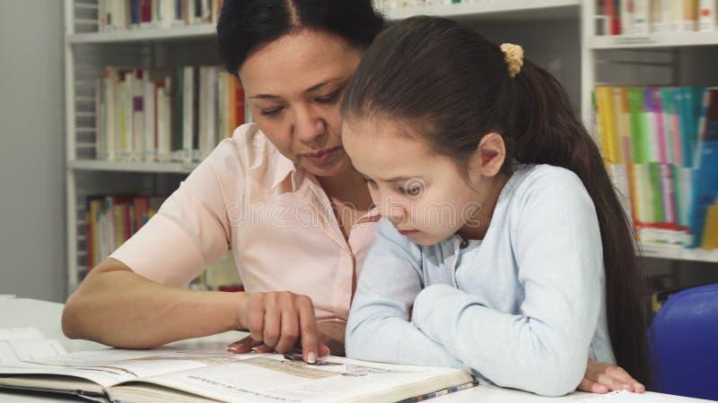 Mujer madura asiática que lee un libro con su hija linda del litlle foto de archivo