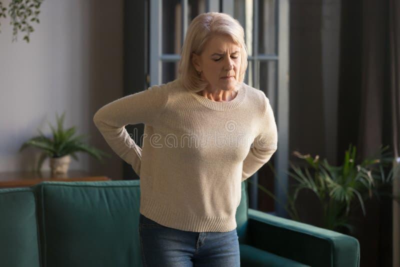 Mujer madura cabelluda gris infeliz que toca detrás, sufriendo de dolor de espalda fotos de archivo libres de regalías