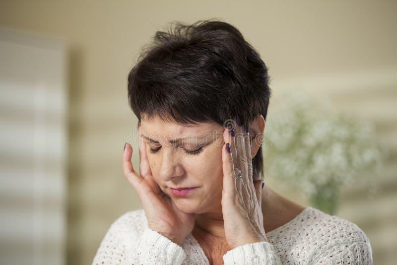 Mujer madura con dolor de cabeza foto de archivo libre de regalías