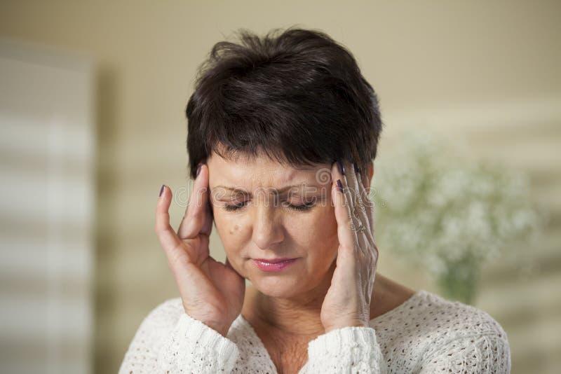 Mujer madura con dolor de cabeza fotos de archivo