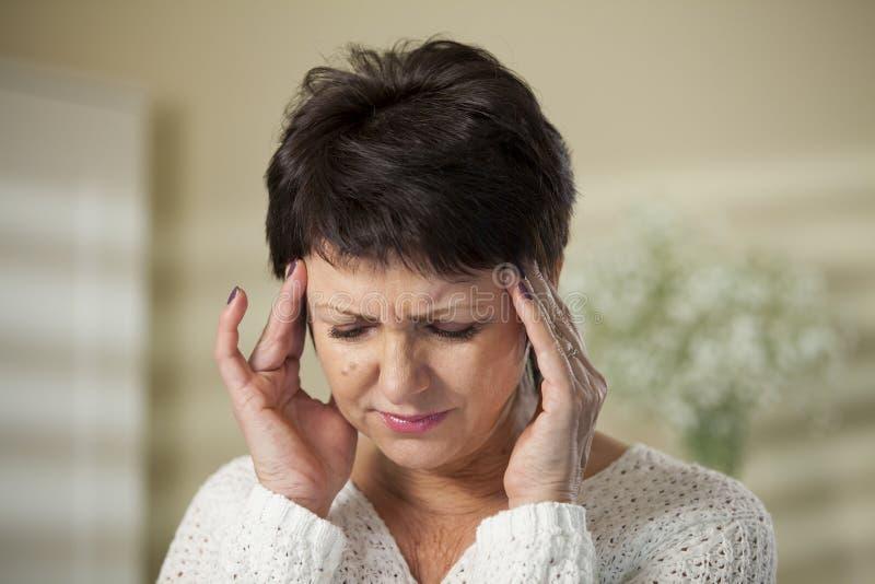 Mujer madura con dolor de cabeza fotografía de archivo