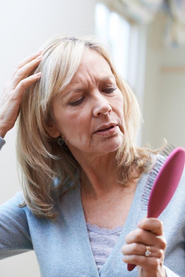 Mujer madura con el cepillo Corncerned sobre pérdida de pelo foto de archivo