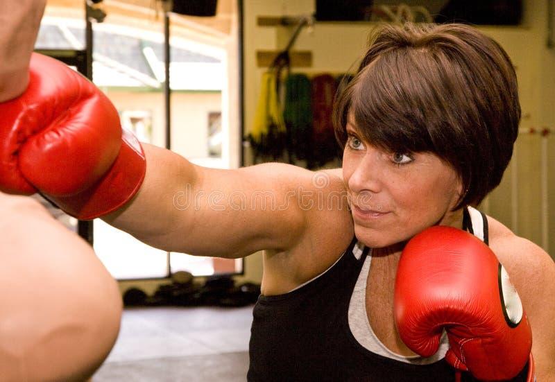 Mujer madura con el maniquí del boxeo imagen de archivo libre de regalías