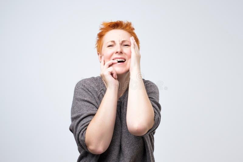 Mujer madura con el pelo rojo corto que sufre de la tensión o un dolor de cabeza que hace muecas en el dolor que lleva a cabo las fotografía de archivo libre de regalías