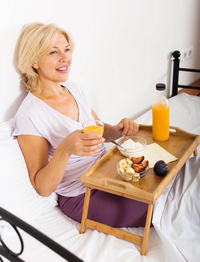 Mujer madura con el zumo, las bayas y el yogur de naranja foto de archivo