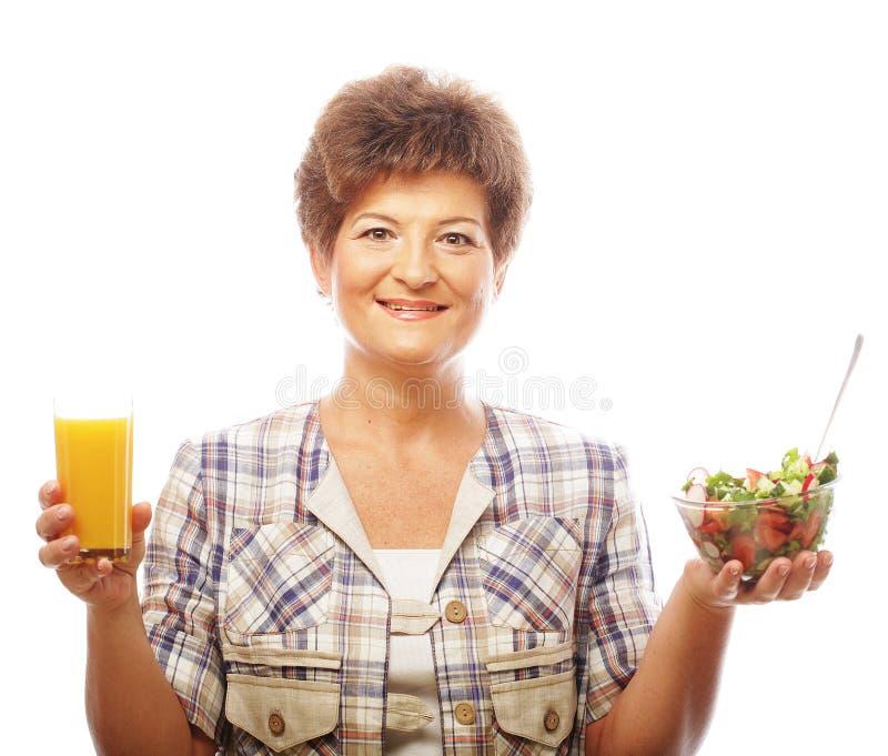 Mujer madura con la ensalada y el jugo fotos de archivo