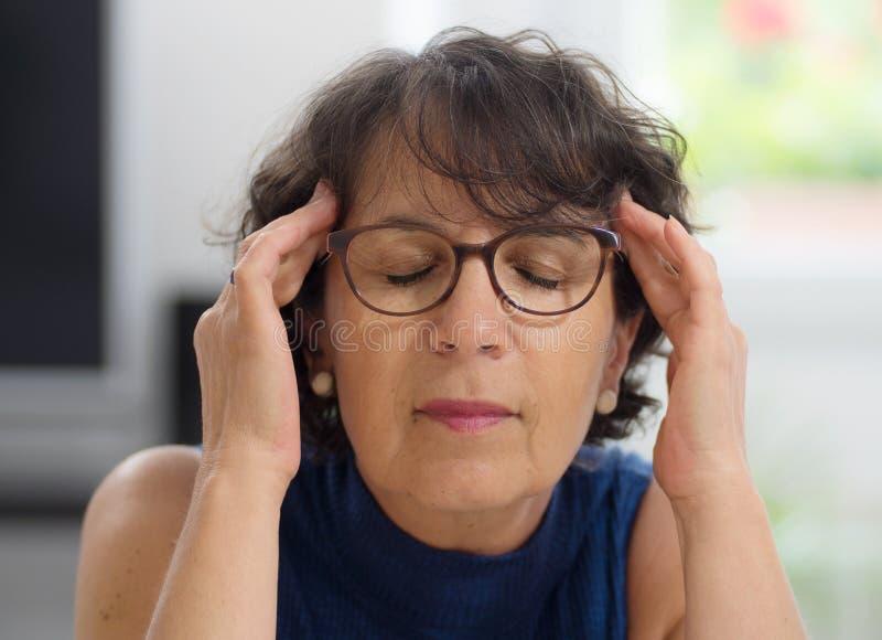 Mujer madura con un dolor de cabeza fotografía de archivo