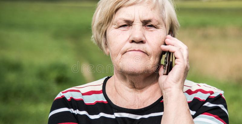Mujer madura de la mirada confiada que habla en un teléfono imagen de archivo