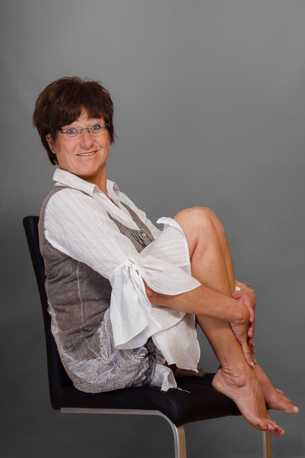 Mujer madura divertida en silla descalzo foto de archivo