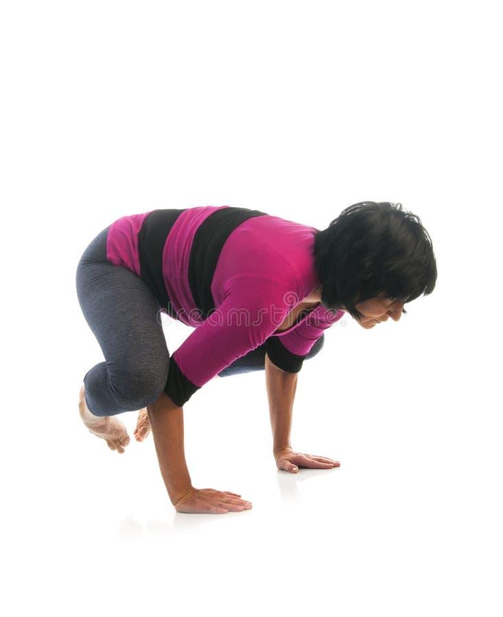 Mujer madura en actitud de la yoga de Bakasana imagen de archivo libre de regalías