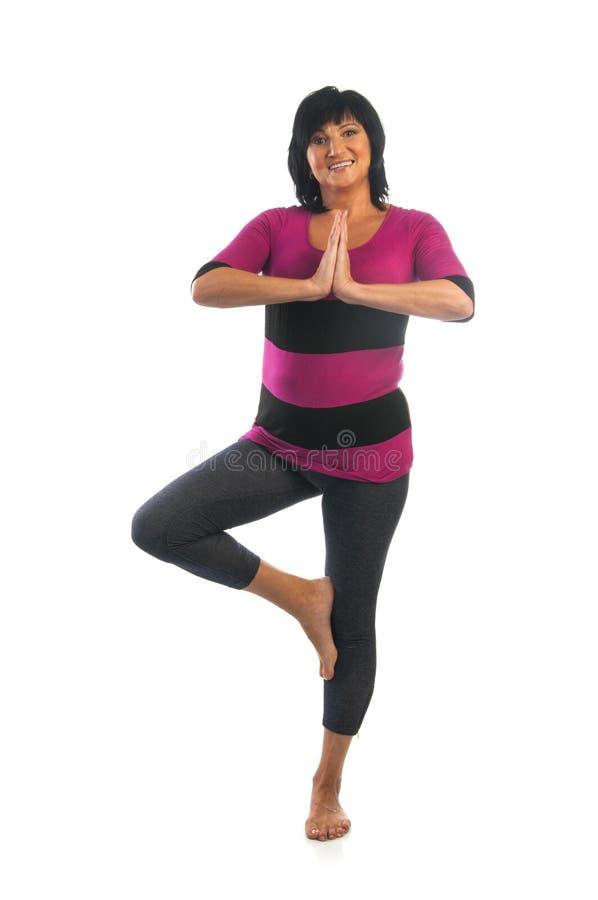 Mujer madura en actitud de la yoga de Vrikshasana imagen de archivo