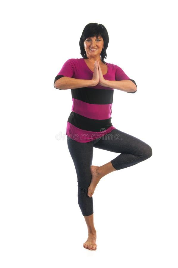 Mujer madura en actitud de la yoga de Vrikshasana imagen de archivo libre de regalías