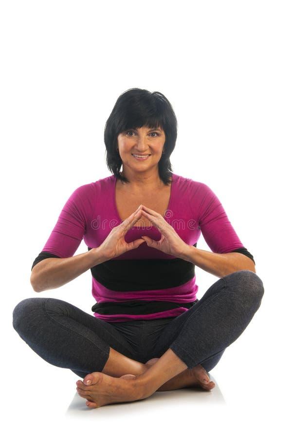Mujer madura en actitud fácil de la yoga imagen de archivo libre de regalías