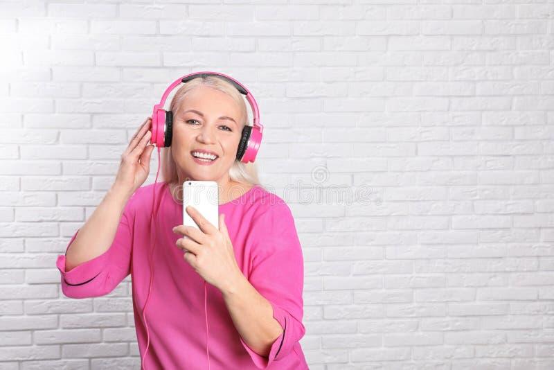 Mujer madura en auriculares con el dispositivo móvil contra la pared de ladrillo imagenes de archivo