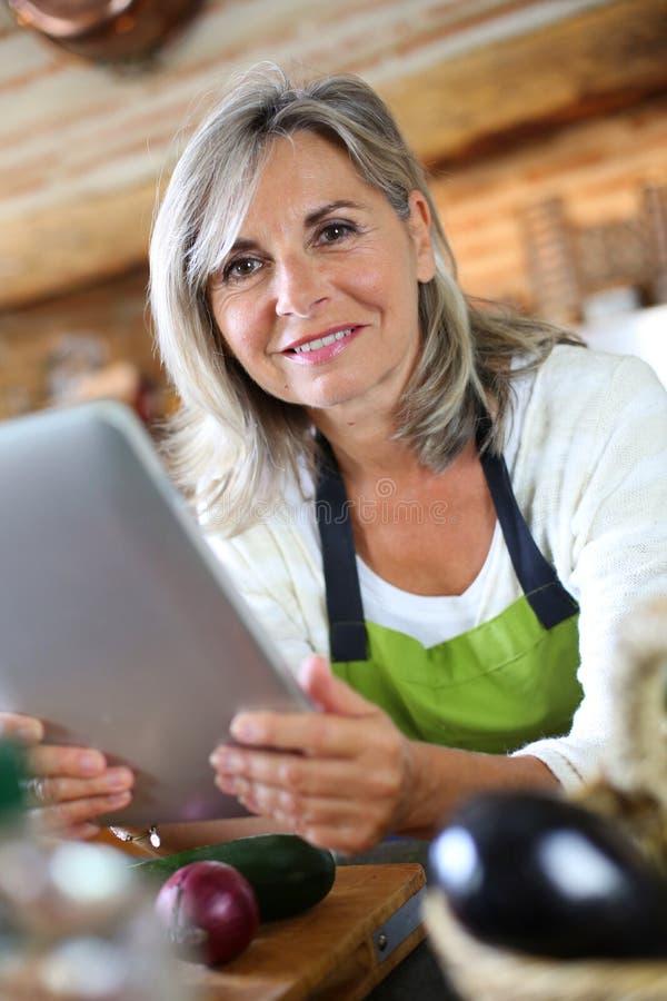 Mujer madura en cocina que comprueba receta en Internet imagen de archivo libre de regalías