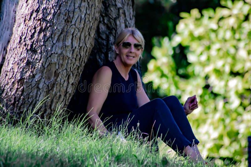 Mujer madura en inclinarse sonriente que se sienta del parque detrás en un registro, rubio con los vidrios y vestido en negro fotos de archivo