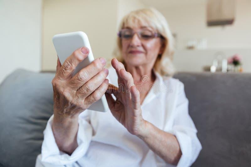 Mujer madura en lentes usando el teléfono móvil imagen de archivo libre de regalías