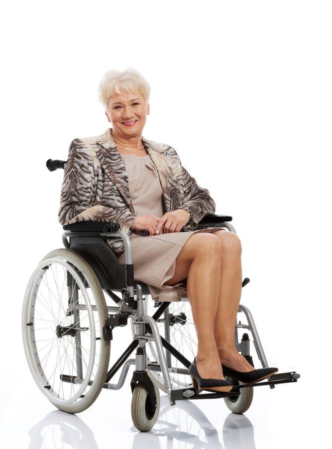 Mujer madura en su sillón de ruedas fotos de archivo