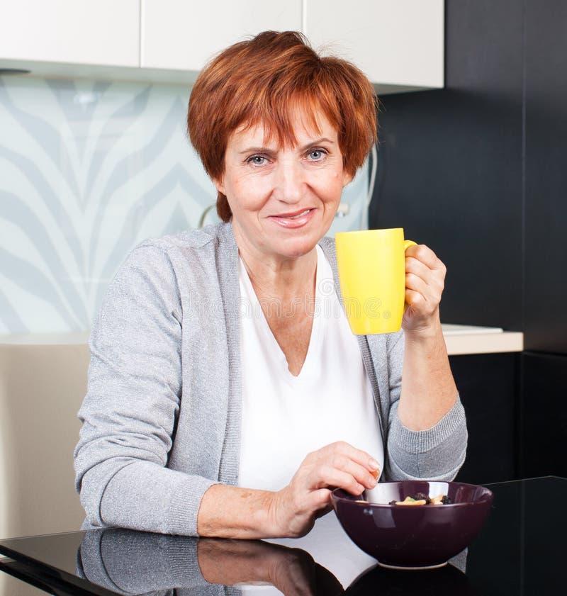 Mujer madura feliz en cocina imágenes de archivo libres de regalías