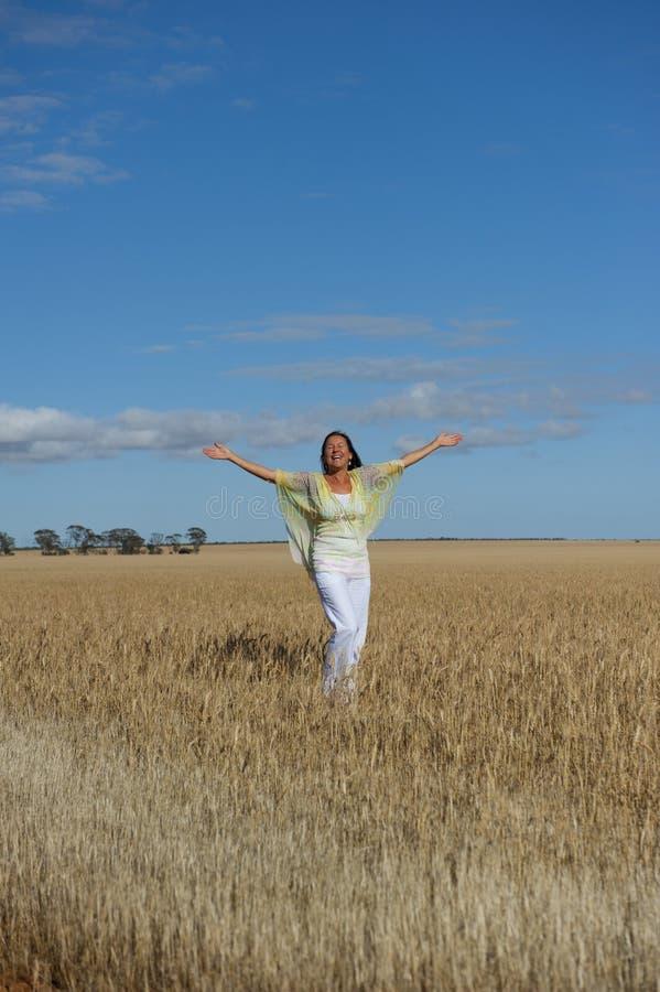Mujer madura feliz en el campo del trigo fotos de archivo libres de regalías