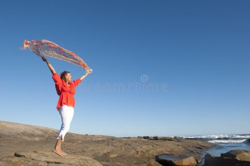 Mujer madura feliz en el mar imagenes de archivo
