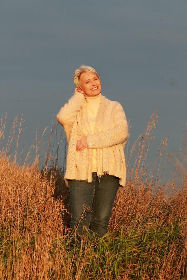 Mujer madura feliz en el sol de igualación fotografía de archivo libre de regalías