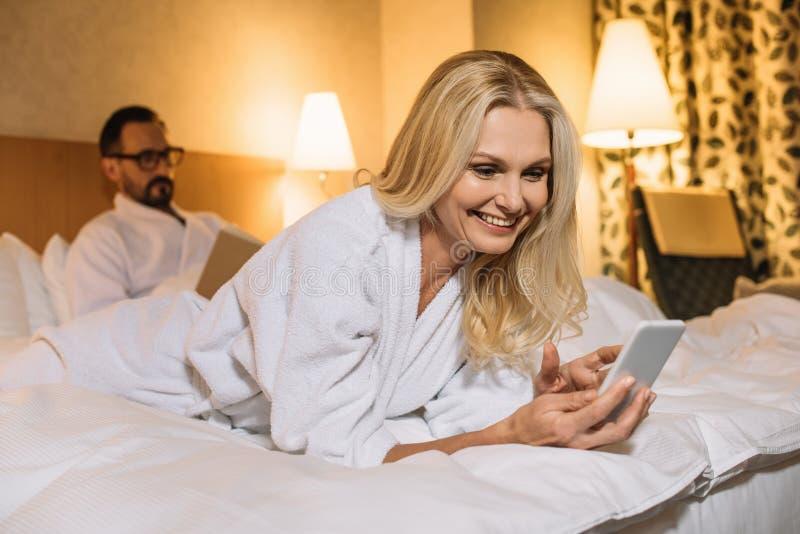 mujer madura feliz en la albornoz que miente en cama y que usa smartphone mientras que libro de lectura del marido fotos de archivo