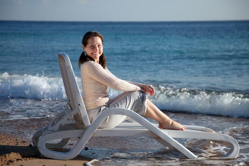 Mujer madura feliz en la playa del mar fotografía de archivo