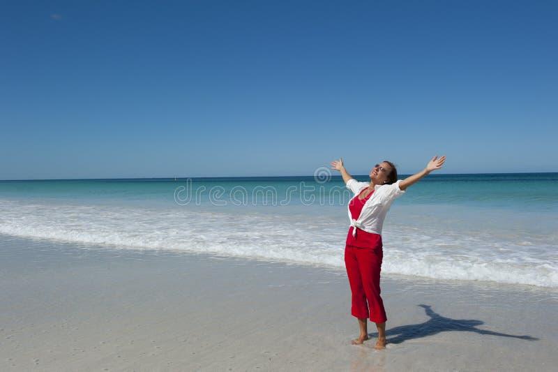 Mujer madura feliz en la playa tropical imagenes de archivo