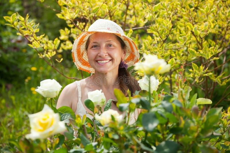Mujer madura feliz en planta de las rosas fotografía de archivo