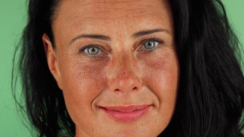 Mujer madura feliz magnífica con los ojos hermosos que sonríe a la cámara foto de archivo libre de regalías