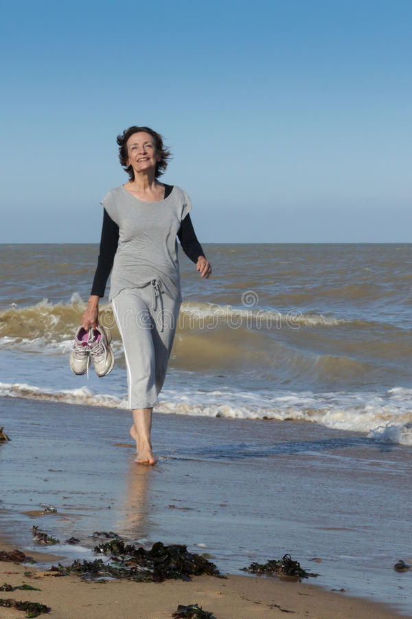 Mujer madura feliz que camina en el mar foto de archivo