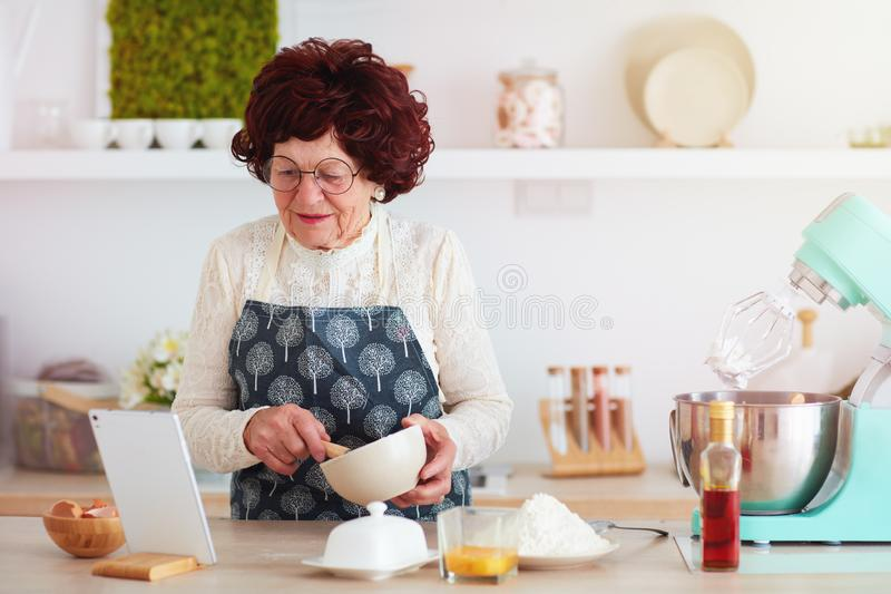 Mujer madura feliz que cuece con la ayuda de Internet, receta de observaci?n en la tableta fotografía de archivo