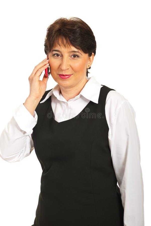 Mujer madura feliz que habla con la célula imagen de archivo
