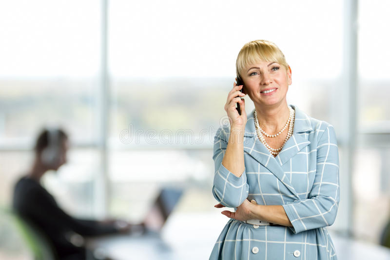 Mujer madura feliz que habla en el teléfono celular imagen de archivo libre de regalías