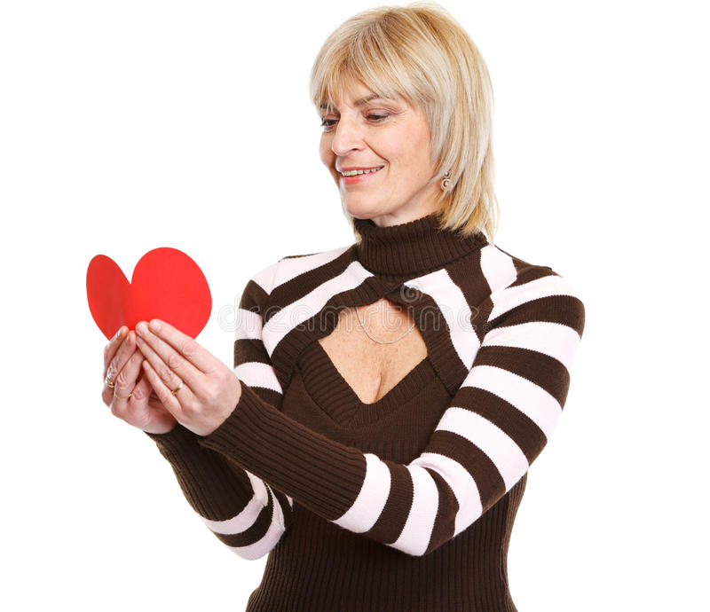 Mujer madura feliz que lee la postal en forma de corazón fotografía de archivo