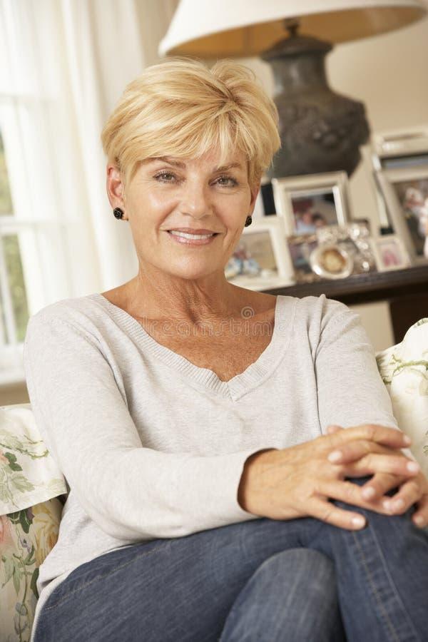 Mujer madura feliz que se sienta en Sofa At Home imagen de archivo libre de regalías