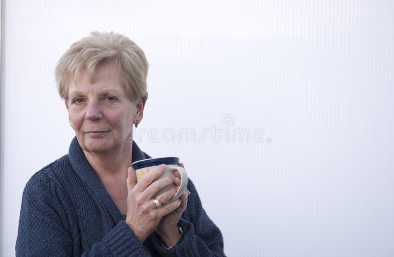 Mujer madura feliz que sostiene una taza de café imagen de archivo libre de regalías