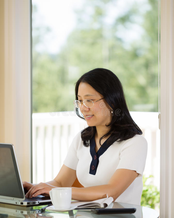 Mujer madura feliz que trabaja de hogar imagen de archivo libre de regalías
