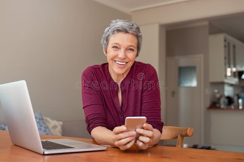 Mujer madura feliz que usa smartphone imágenes de archivo libres de regalías